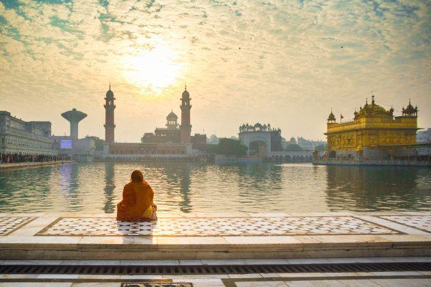 Una mujer reza ante el Templo Dorado de Amritsar,