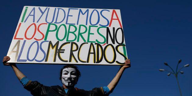 Un manifestante del movimiento 15-M sujeta una pancarta que