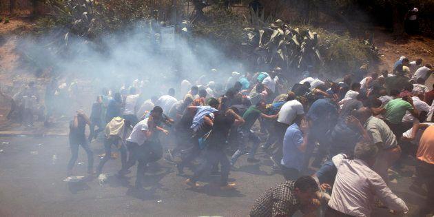 Varios palestinos se dispersan mientras la policía fronteriza israelí dispara granadas detonadoras durante...