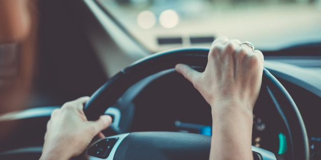 Brunette woman driving a car automobile interior hands on