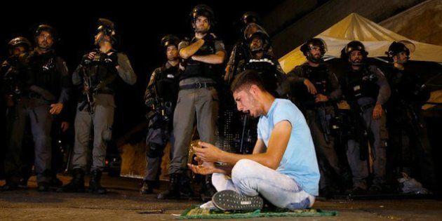 Un joven palestino reza ante la Puerta de los Leones de Jerusalén ante la mirada de la Policía de Fronteras...