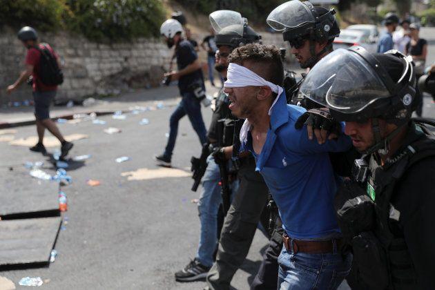 Un palestino es conducido por policías israelíes, tras ser detenido a las afueras de las murallas de