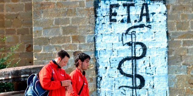 Imagen de archivo de dos personas pasando junto a una pintada de ETA en el pueblo vasco de
