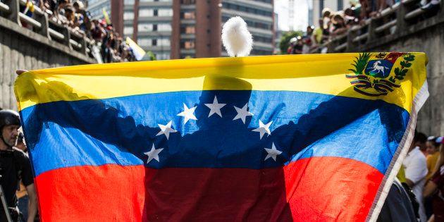 Una persona extiende una bandera venezolana ante decenas de manifestantes