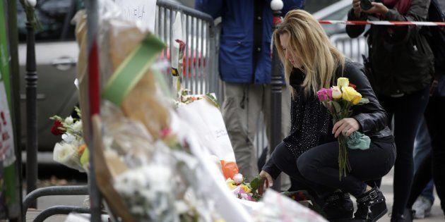 Imagen de archivo de una mujer dejando flores en París en recuerdo de las víctimas de los atentados de...