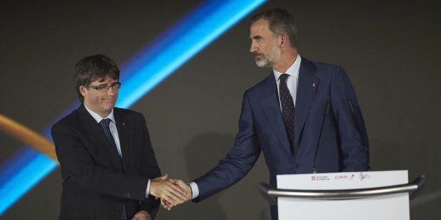 El rey Felipe y el president catalán, Carles Puigdemont, se saludan en el acto de recuerdo de Barcelona