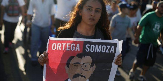 Una manifestante con cartel que compara a Ortega con el dictador