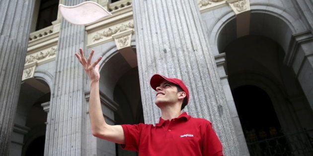 Un pizzero de Teletpizza enfrente del edificio de la Bolsa de Madrid antes del debut bursátil de la compañía...