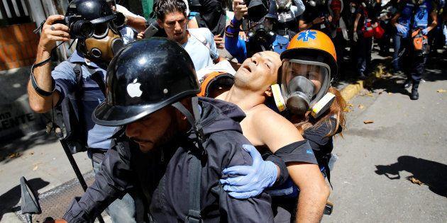 Un hombre herido en una manifestación contra el Gobierno en Caracas es llevado a una moto para ser tratado...