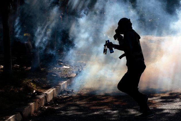 Un manifestante corre entre el gas lacrimógeno durante una manifestación en Barquisimeto
