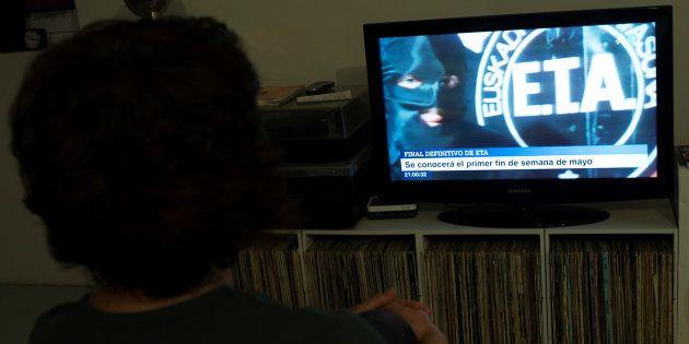 Una mujer ve en la tele un programa sobre el fin de