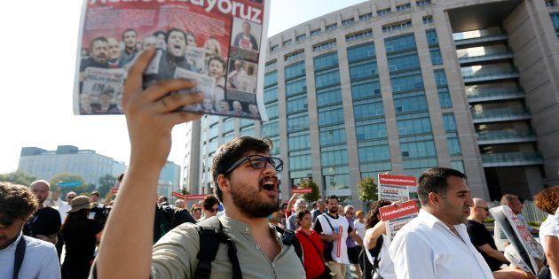 Un hombre muestra un ejemplar del 'Cumhuriyet' durante una concentración delante del Palacio de Justicia...