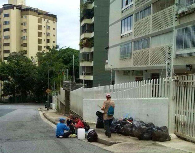 Hombres comiendo de la basura en una calle de
