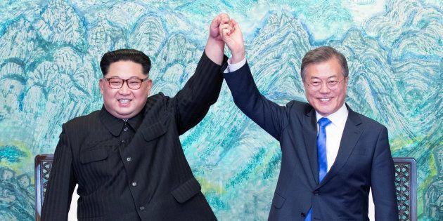 El presidente surcoreano Moon Jae-in y el líder norcoreano Kim Jong-un estrechan y alzan sus
