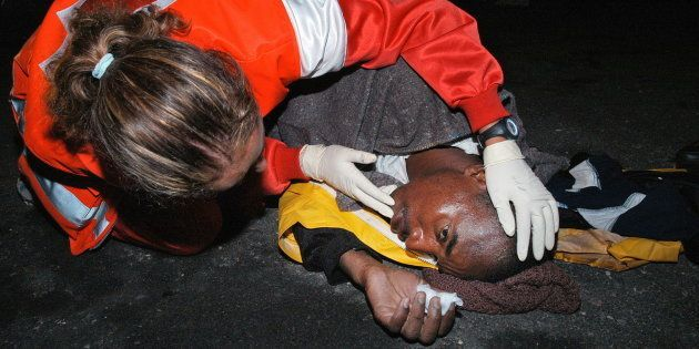 Una miembro de Cruz Roja atiende a un subsahariano llegado al puerto de Arguineguin, Gran Canaria, en...