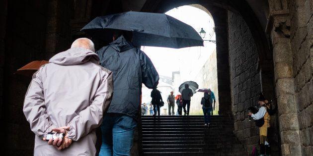 Un grupo de turistas con paraguas accede a la Plaza del Obradoiro de Santiago, en una imagen de