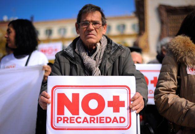 Un hombre sujeta una pancarta que dice 'No más precariedad' en una manifestación en