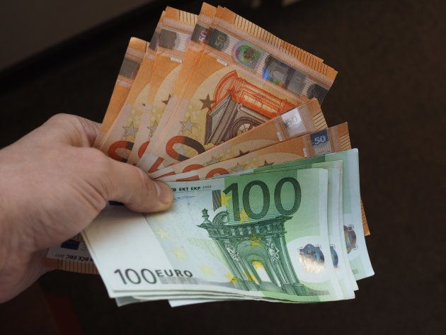 Hand holding and giving Euro banknotes money (EUR), currency of European