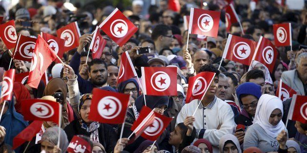 People wave national flags during celebrations marking the fifth anniversary of Tunisia's 2011 revolution,...
