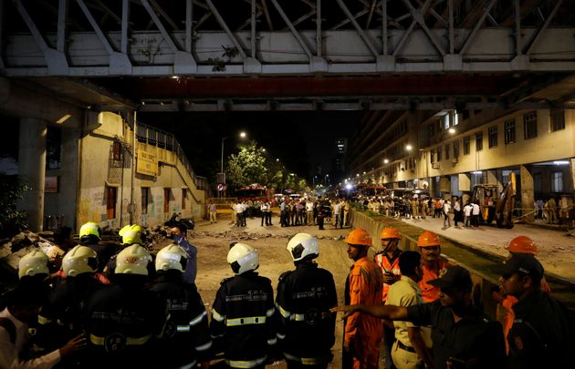 Rescue workers stand at the site of the