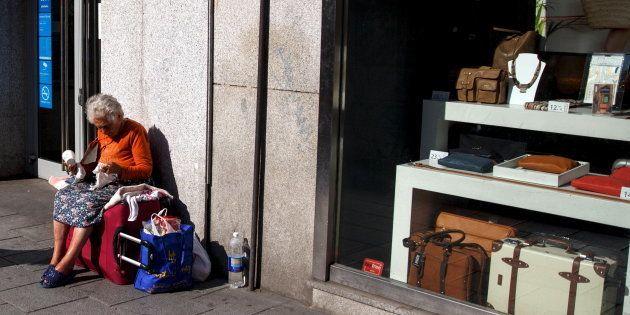 Una mujer pide dinero a las puertas de una tienda de lujo en el centro de Madrid, en una imagen de