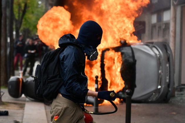 Un manifestante, enmascarado, junto a un coche en llamas, el pasado Primero de Mayo en