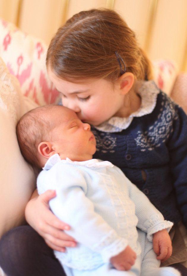 La princesa Carlota da un beso al príncipe Luis al que sostiene en brazos en el día de su cumpleaños,...