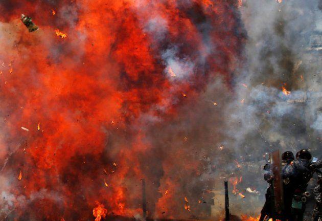 Un grupo de uniformados se protege de las llamas de las protestas, en las puertas de la Asamblea, en