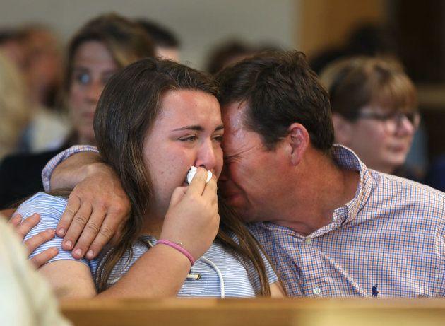 El padre y la hermana de la víctima lloran durante el
