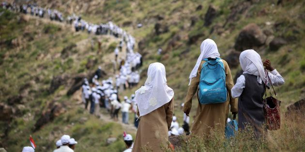Voluntarios yemeníes forman una cadena humana para transportar la ayuda alimentaria que envía la Media...