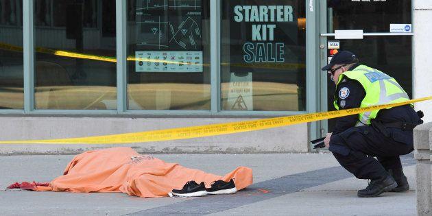 Un agente de policía custodia el cuerpo de una de las víctimas del atropello masivo de Toronto, el pasado...