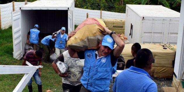 Integrantes de ONU sacan bultos con armas de contenedores en Monteredondo, departamento de Cauca