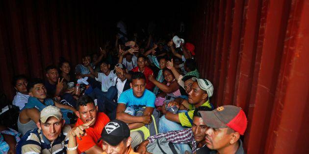 Migrantes hondureños suben a un contenedor para seguir su camino hacia la frontera de
