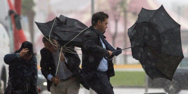 Varias personas sujetan sus paraguas intentando que no se les vuele debido al fuerte viento y a la lluvia...