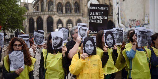 Un grupo de manifestantes con caretas de la activista Samar Badawi y su hermano Raif, bloguero, pidiendo...