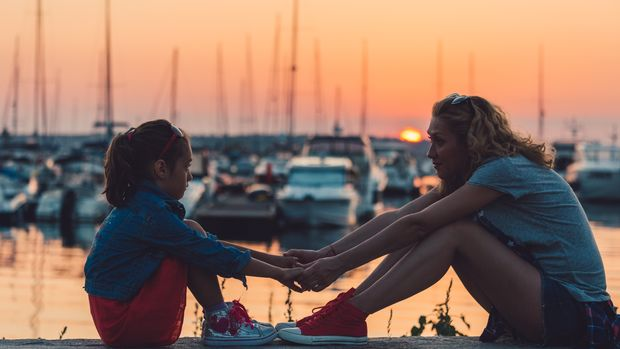 Relaxed mother and daughter at the seaside sitting on sunset and holding hands