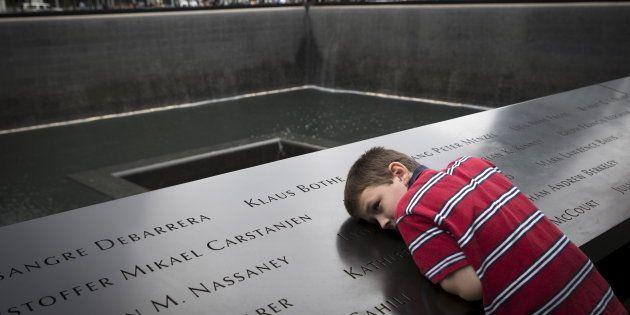 Un niño se inclina sobre el memorial de las víctimas del 11-S en Nueva York, en el aniversario del atentado...