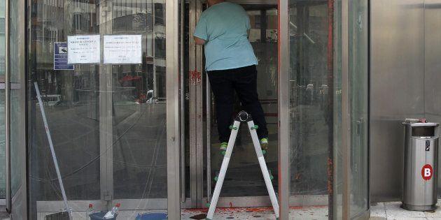 Un operario limpia las pintadas que un grupo de desconocidos ha realizado hoy en la sede de la Agencia...