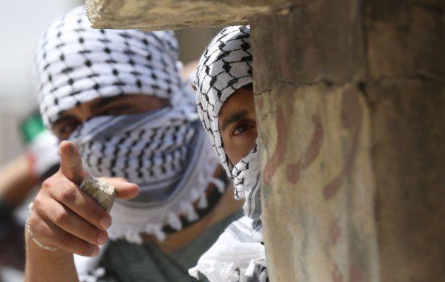 Manifestantes palestinos a cubierto durante las