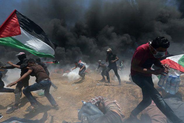 Un grupo de manifestantes palestinos escapa ante los disparos y los botes de humo lanzados por