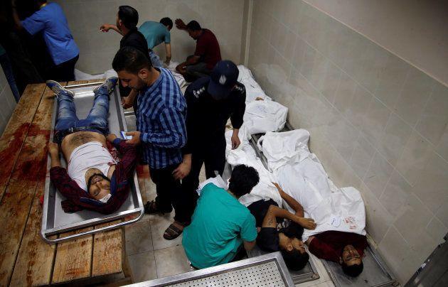 Un grupo de palestinos identifican los cuerpos de varios de los muertos hoy en la frontera con Israel,...