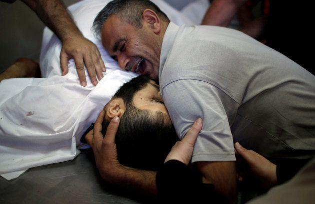 El hermano del palestino Shaher al-Madhoon, muerto en las protestas de hoy, llora en una morgue del norte...