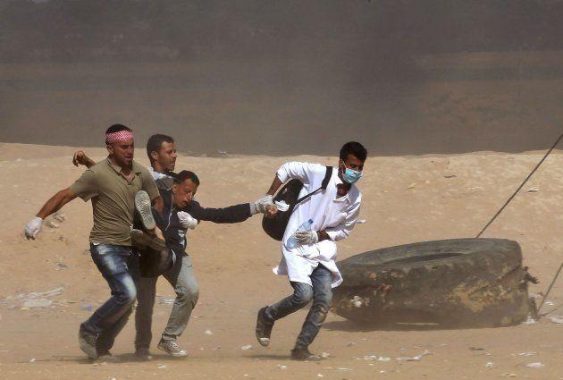 Varias personas trasladan a un herido cerca de la valla con Israel en la Franja de