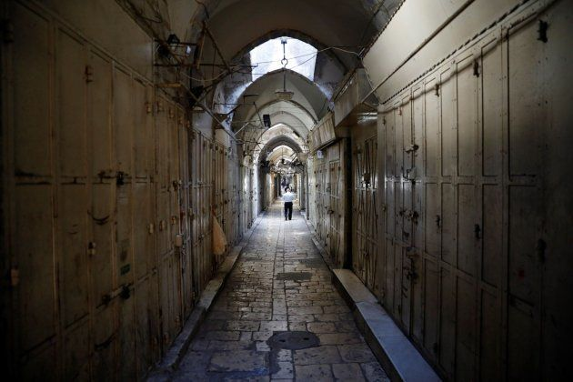 Un palestino camina entre las tiendas, que permanecen cerradas, del mercado de la Ciudad Vieja de
