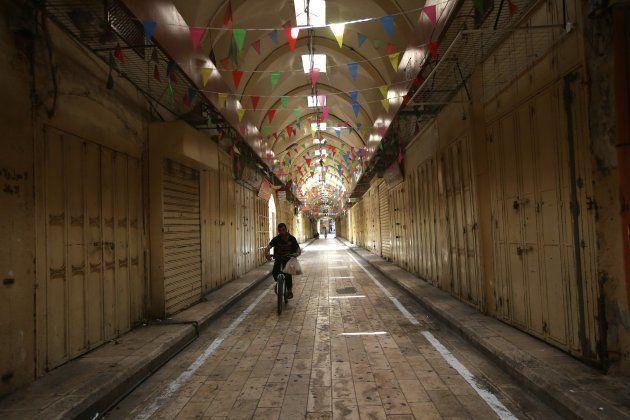 Un palestino circula en bicicleta por una calle con todos los comercios cerrados en Nablus,