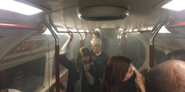 Usuarios del metro, tapándose la cara para no respirar el humo en