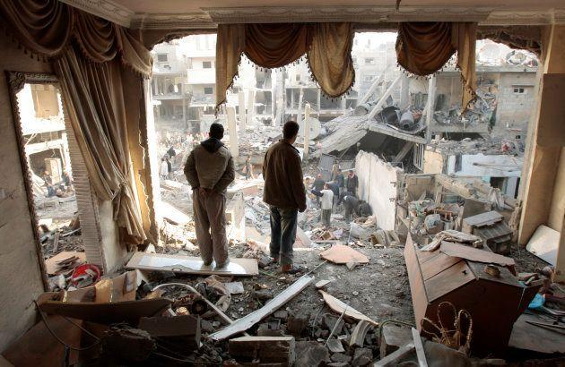 Un grupo de palestinos revisas sus casas, destrozadas en la Operación Plomo Fundido de