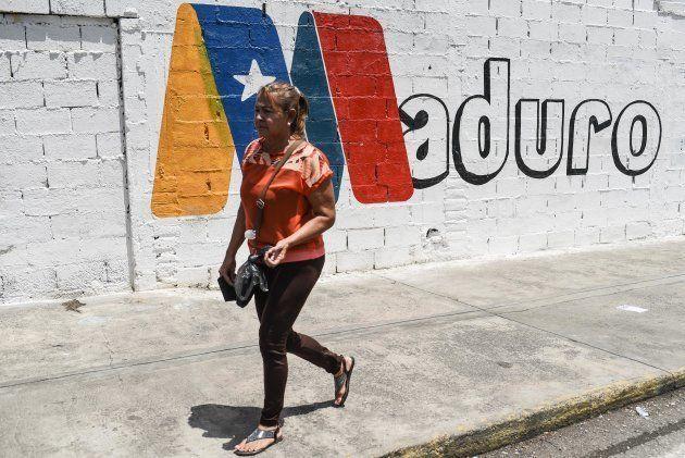 Una mujer pasa ante un mural de apoyo a Maduro en Charallave, estado de Miranda, el pasado 15 de