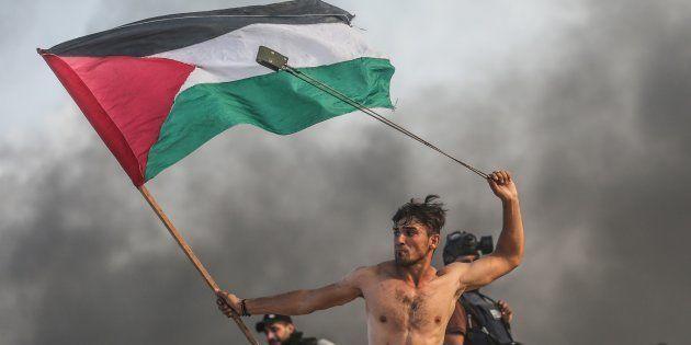 Aed Abu Amro, lanzando piedras y enarbolando la bandera de Palestina en una protesta en Gaza, el pasado...