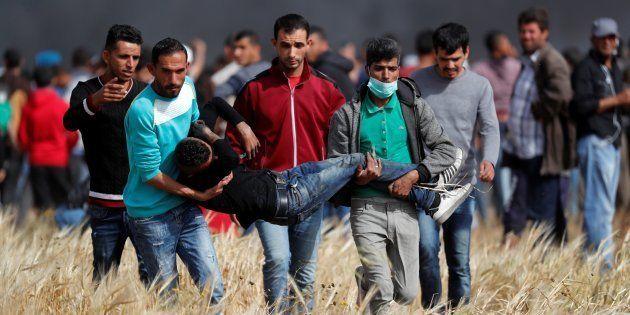 Un grupo de palestinos traslada a un joven alcanzado por la carga de los soldados del Israel, el pasado...